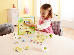 interior shot of girl sitting at table placing a tile into a box while playing a board game.