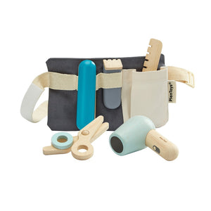 on a white background, a dark grey canvas belt bag with natural coloured strap with styling tools in the loops. a wooden scissors and hair dryer in the foreground.