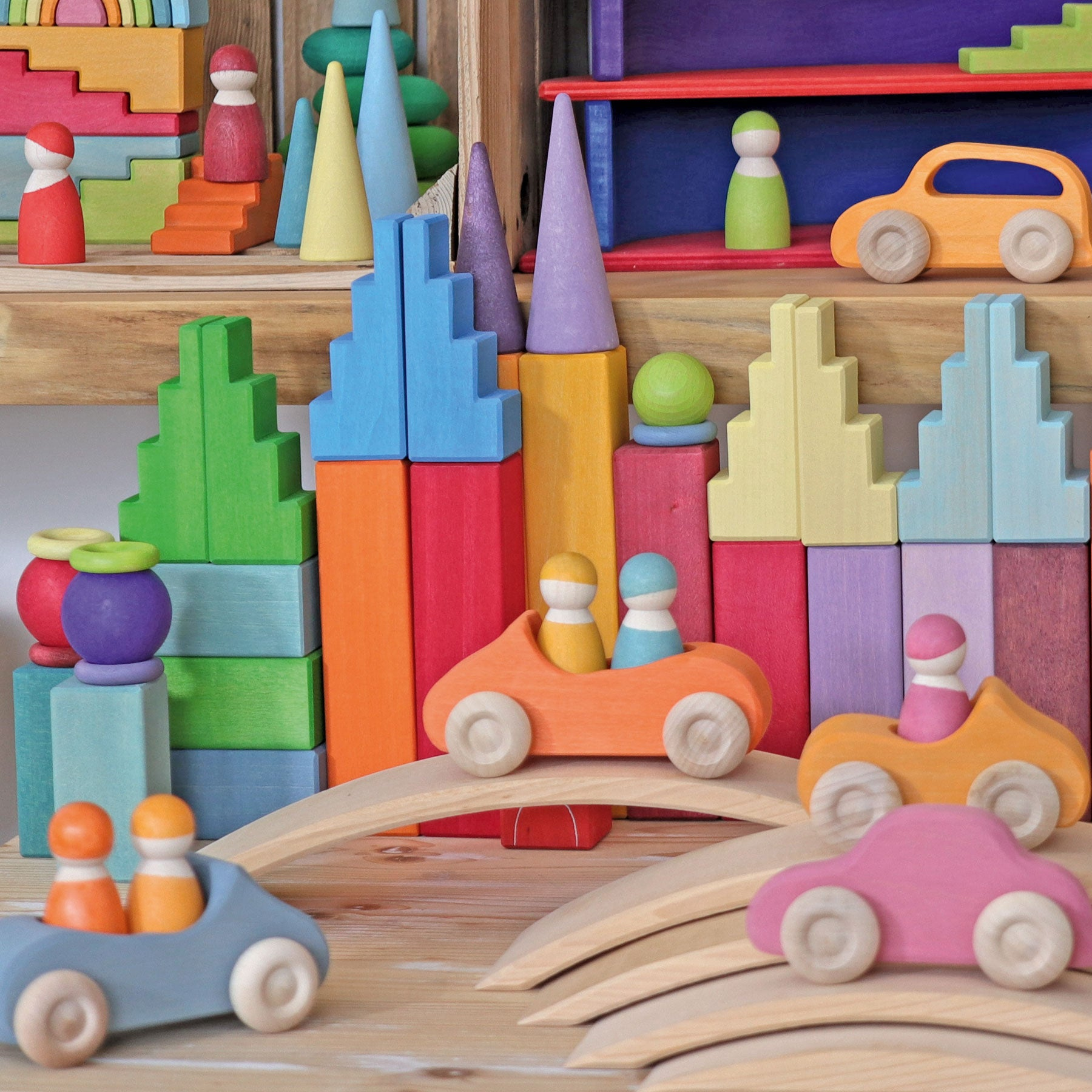 an assortment of grimms rainbow and pastel building blocks, cars and peg people in an interior space.