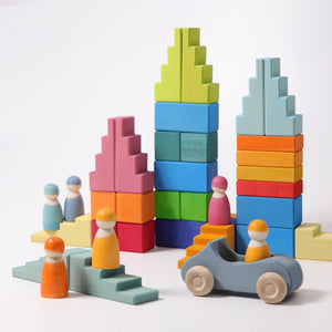 An assortment of rainbow and pastel building blocks and peg people with one car on a white background