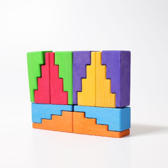 Rainbow coloured stepped building blocks pieced together to creat a rectangular tower on a white background