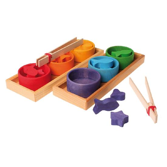 on a white background, two wooden trays with three different coloured bowls filled with matching wooden pieces in each. Two natural wooden tweezers one next to the tray, one on top of the bowls. Three purple wooden pieces next to one of the trays.