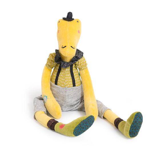 On a white background, a plush, moustachioed, long-legged, lime green crocodile wearing a tiny black bowler hat, a ruffled black and white collar, suspenders, grey shorts, sparkly socks and a watch.