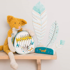 On a wooden shelf in an interior space, a plush fox with long limbs and a pink nose sits next to a white kalimba. A blue harmonica is beside it. On the wall are some painted feathers in white and soft blue