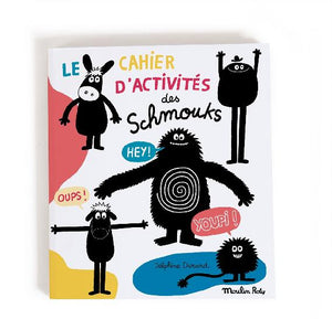 On a white background, a book with splotches of colour and illustrated black and white monsters