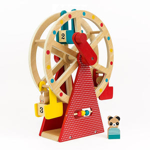on a white background a wooden ferris wheel with a red base with small white polka dots and a red wooden crank handle. Three numbered cars in yellow, blue and red. A wooden panda figure in the foreground.