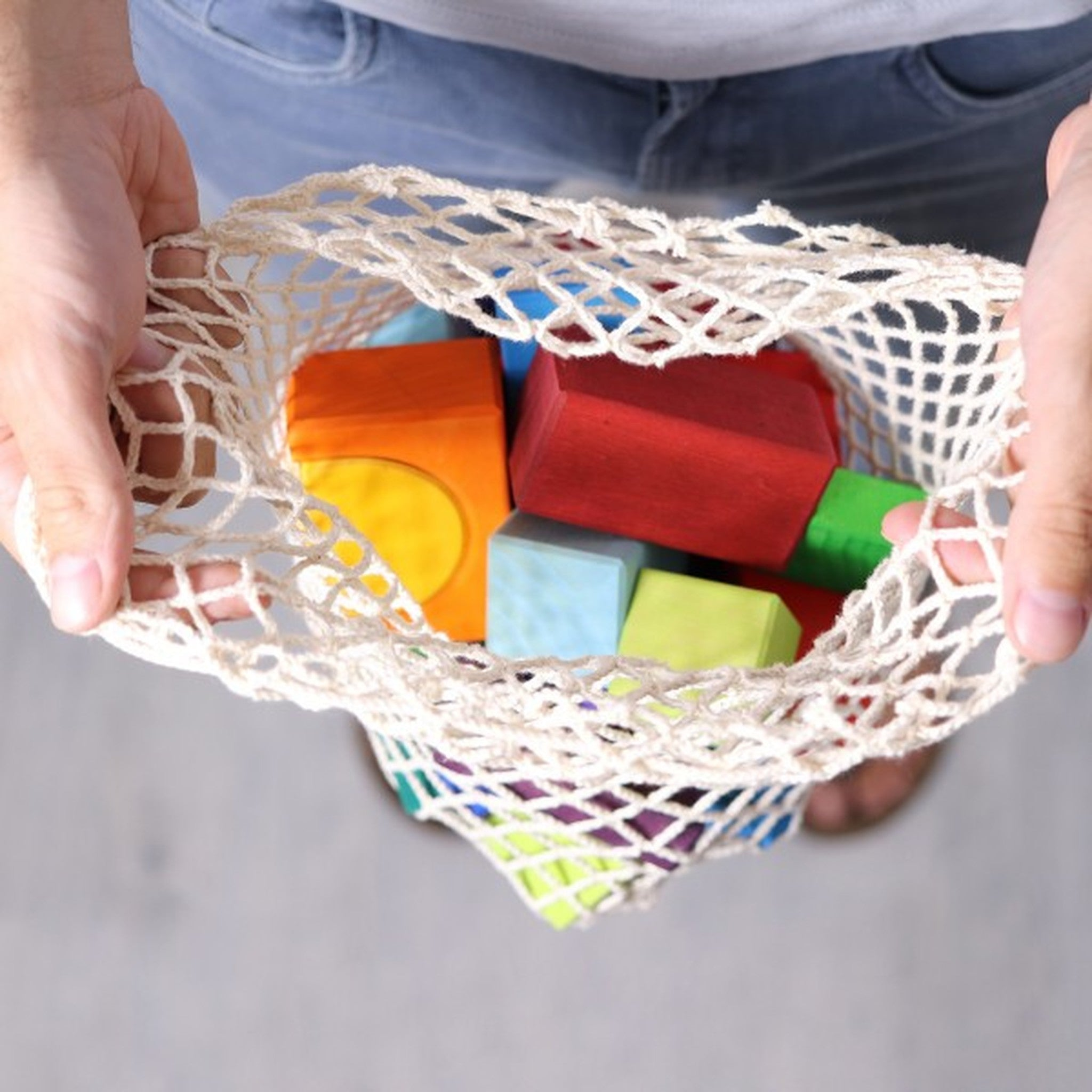 A child holding the open net bag that is storing the blocks on a white background.