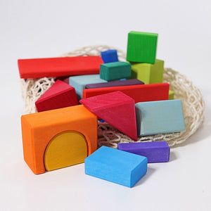 Some brightly coloured blocks in a pile on a white background. A net bag sits behind them.