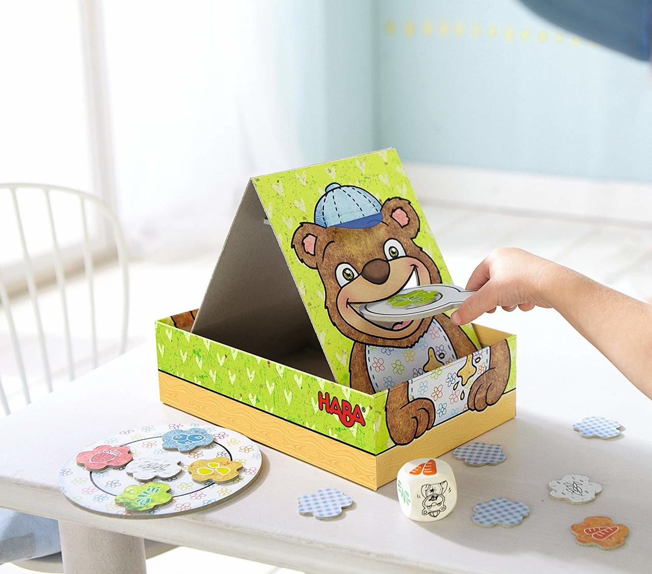 interior shot, a child's hand using a flat spoon to put food into an illustrated bears mouth on the box that is on the table.