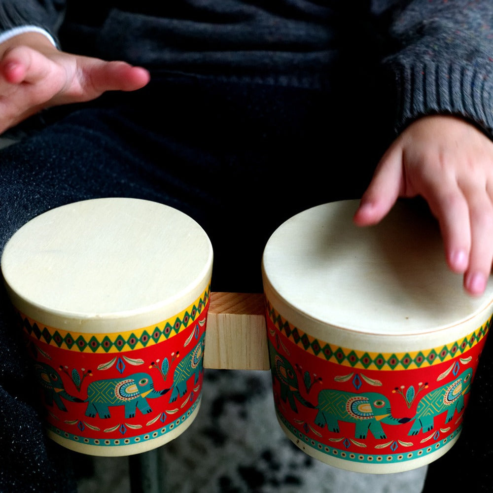 A child wearing a navy blue sweater drumming the bongos.