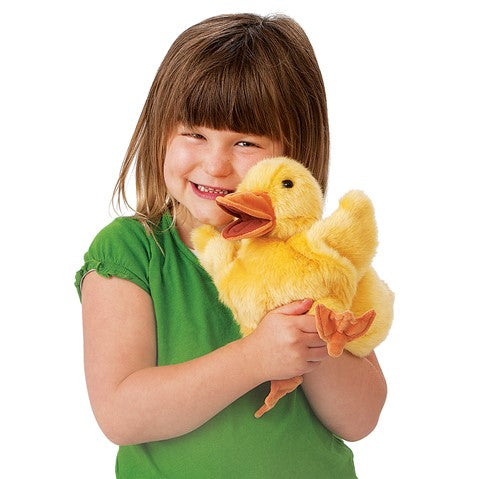 Alittle brown haired girl with bangs hugging a yellow plush duckling