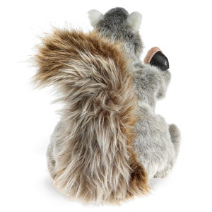 The back of a plush squirrel holding an acorn on a white background