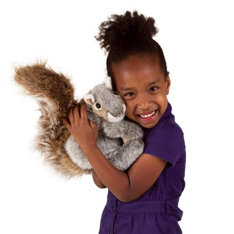 A smiling girl hugging a plush squirrel close to her face on a white background.