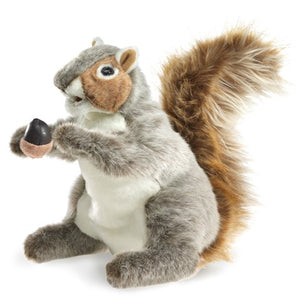 A plush squirrel holding an acorn on a white background