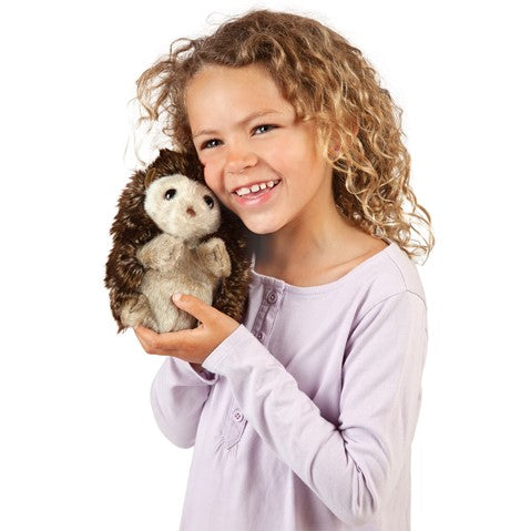 a girl with curly hair holding a plush hedgehog next to her face and smiling on a white background
