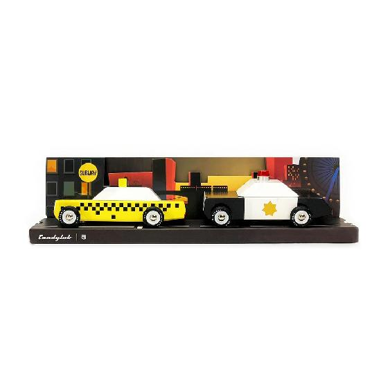 A retro wooden yellow checkered cab and a retro black and white police car on a cardboard road with a city scene behind the cars. On a white background.