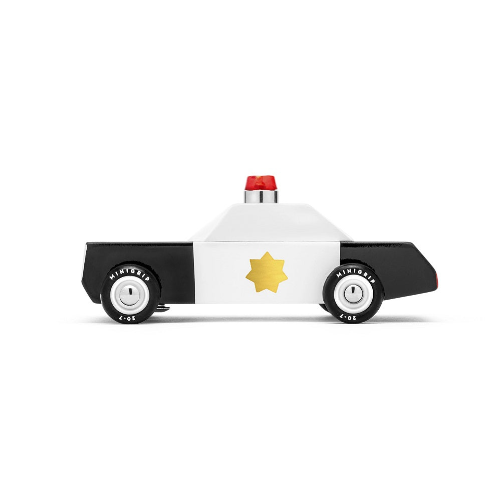 on a white background, a retro black and white cop car with a gold seal on the side and a red light on top.