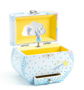 A light blue music box with blue and yellow stars all over it on a white background. The top is open, showing a small unicorn sitting on a cloud.