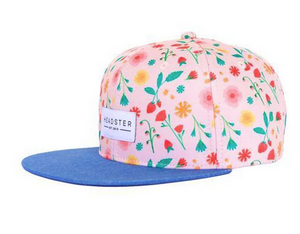 A light pink baseball cap with bright coloured flowers all over it and a denim blue brim on a white background.