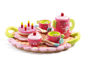 on a white background, a pink and green wooden tea set on a tray with two cups, teabags, spoons, a cake with candles, a teapot and a covered sugar dish