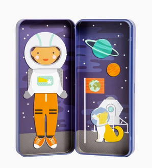 The open box with the same girl wearing the same outfit but now with a helmet. On the other side of the box, there is a dog wearing a space helmit and a flag stuck in the ground, a spaceship behind them in space. On a white background.