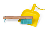 A handbroom laying inside of a dustpan on a white background.