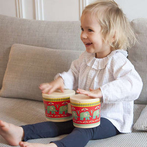 A little girl in a white shirt and navy leggings sitting on a gray couch banging the drums.