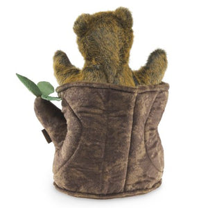 The back of a brown, plush bear cub in a soft tree stump with three green leaves on a white background.