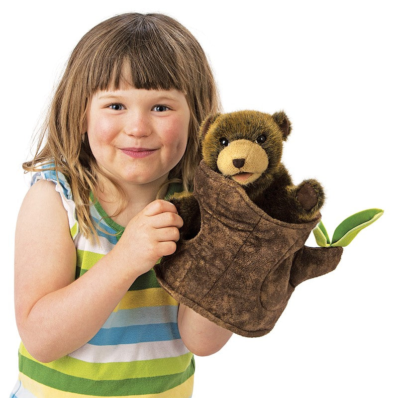 A little girl with brown hair and bangs in a striped tank top with her hand in the bottom of a brown, plush bear cub in a soft tree stump with two green leaves on a white background.