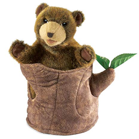A brown, plush bear cub in a soft tree stump with two green leaves on a white background.