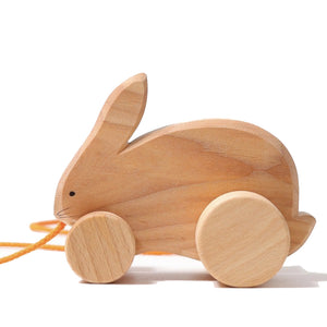 Grimm's bobbing rabbit, natural wooden bunny rabbit on wheels with an orange cord to be pulled by. Simple painted eyes and whiskers.