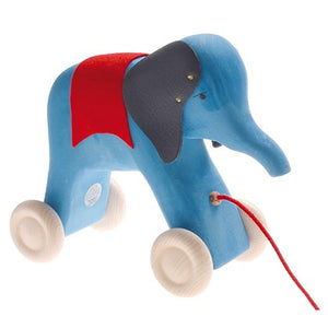 a wooden blue elephant on wheels with a red fabric over its back with leather ears held on by gold tacks. Painted eyes and a red string to be pulled from. On a white background