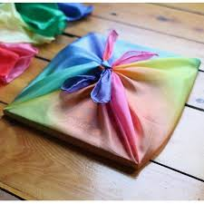 on a wooden floor, a flat square package wrapped in a gradient rainbow silk tied on the top.