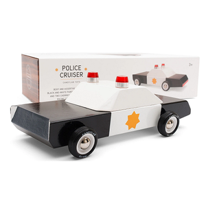 On a white background, a wooden, boxy black and white police car with a gold star on the side and two red lights on top. Its box is in the background