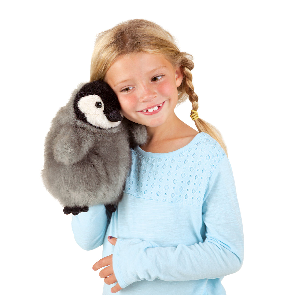 a smiling girl with blonde braids holding a plush baby emperor penguin puppet next to her face