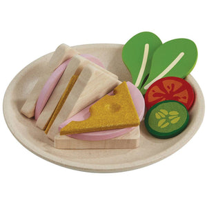 On a white background, a wooden plate with a wooden cheese and meat triangle sandwich on it. Also a wooden slice of tomato, cucumber and two lettuce leaves