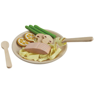 on a white background, a pretend pasta dinner on a wooden plate with noodles, salmon, mushrooms, asparagus and lemon slice. A spoon is next to the plate and a fork is twirling some noodles