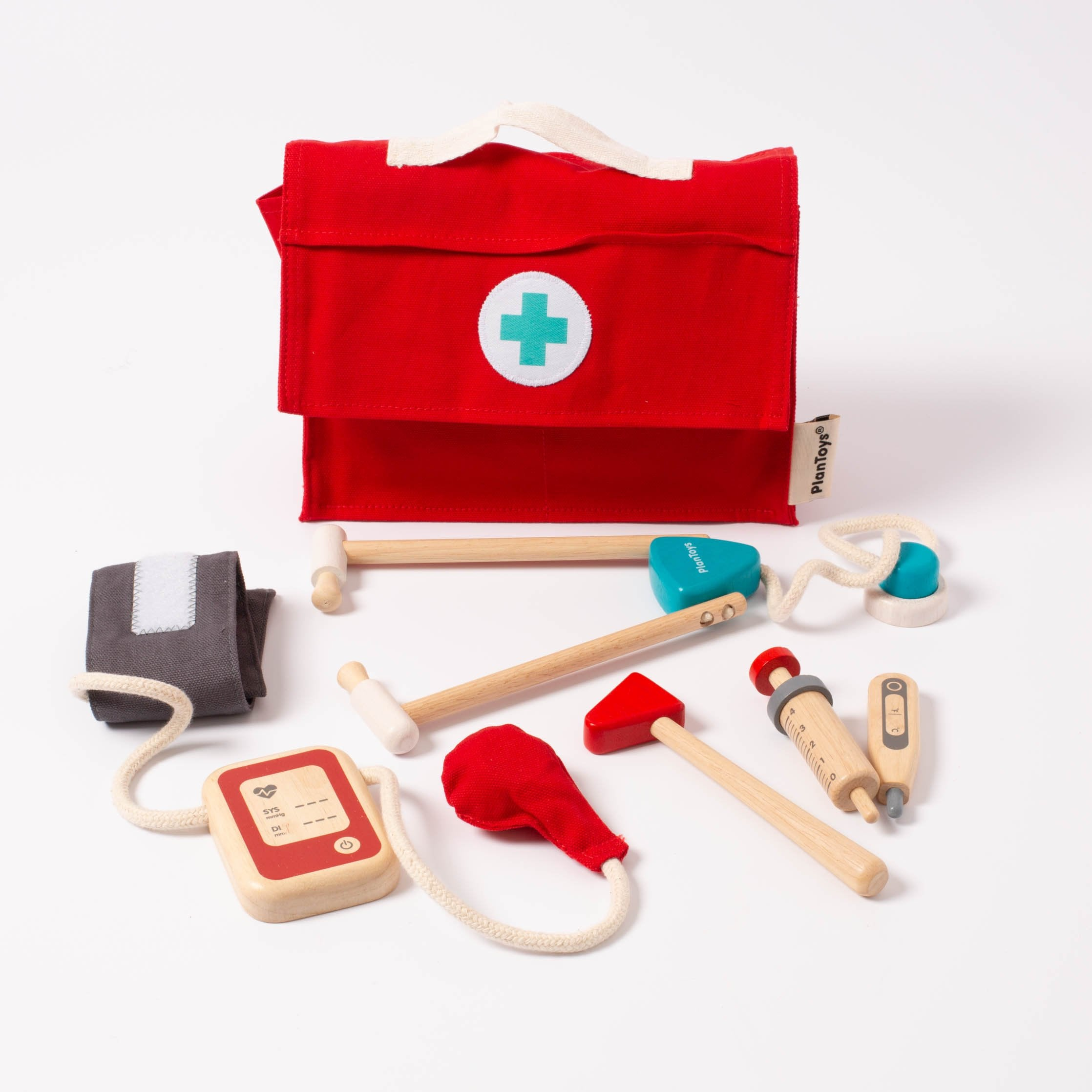 Five wooden and/or cotton doctor tools arranged in a white setting. Also shown is a red, cotton doctor's bag with a handle on top and a croos on the front