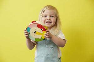 A little blonde girl shaking the tambourine on a yellow background.