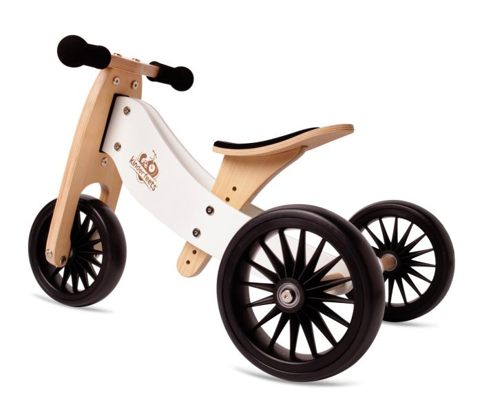 A wooden trike with natural and white colours and black wheels. No pedals