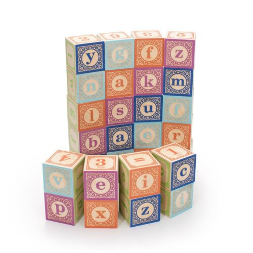 A set of lower case alphabet blocks stacked in a curved wall on a white background with a shorter wall in front. Some blocks show letters and some show numbers with different colours on each face.