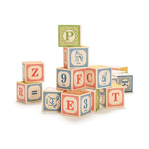 A set of upper case alphabet blocks stacked haphazardly on a white background. Some blocks show animals, some letters, some numbers with different colours on each face.