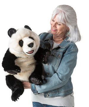 On a white background, a woman holding A giant black and white realistic plush panda