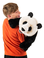 On a white background, a boy holding over his shoulder a giant black and white realistic plush panda