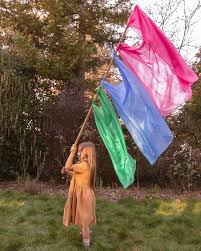 a girl in a forest holding a long stick with playsilks tied to it like a flag