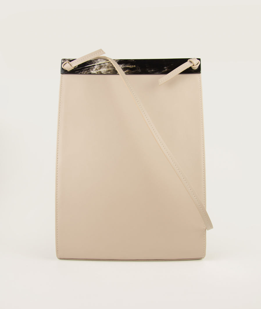 Frontside of Gwyneth bag, size L, in soft light beige, made from Italian smooth calf leather. This size is perfect suitable for A4 formats and all iPad sizes. Shoulder strap is also in the function of easy closing and opening the bag.