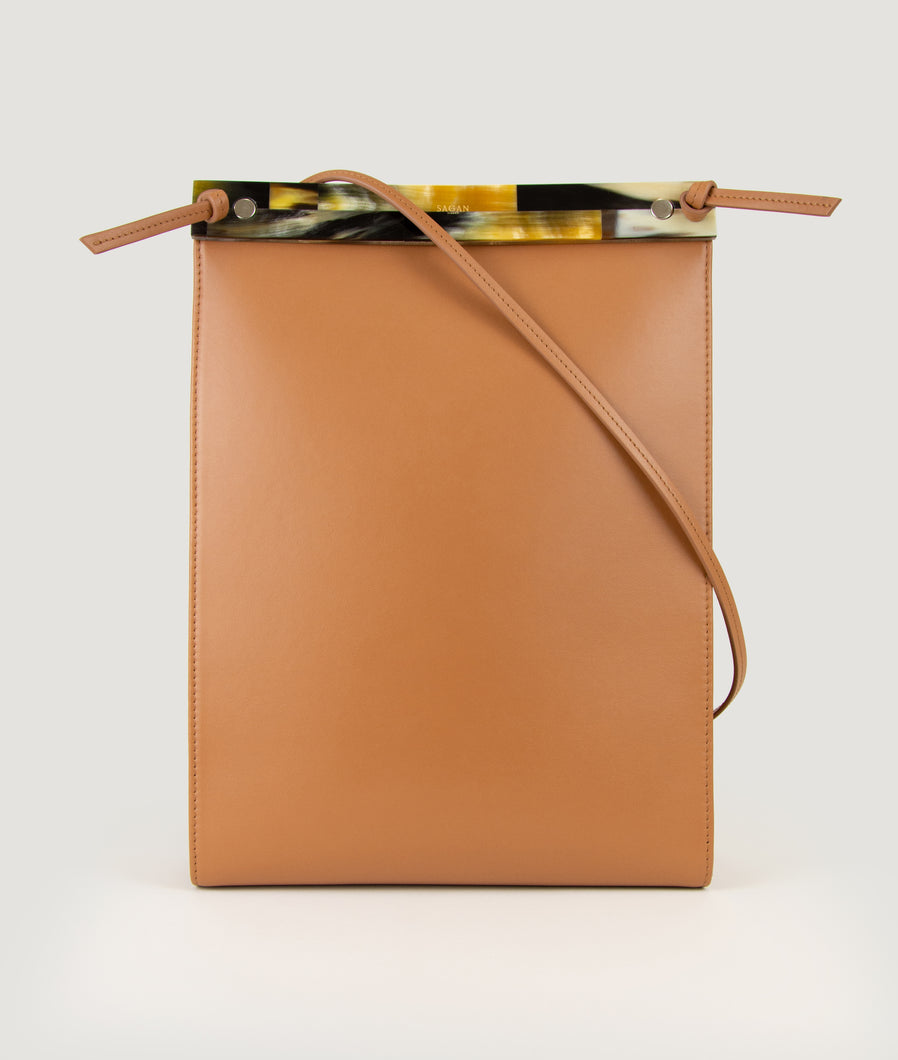 Gwyneth bag, size L, in camel, made from Italian smooth calf leather. This size is suitable for A4 formats and all iPad sizes. The front plate is hand made from horn. Elegant and contemporary.