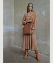 Load image into Gallery viewer, Gwyneth bag, size L, in camel, made from Italian smooth calf leather. This size is suitable for A4 formats and all iPad sizes. The front plate is hand made from horn. Elegant and contemporary.