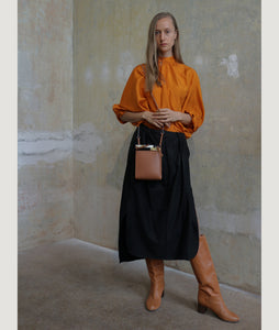 Gwyneth bag, crossbody bag, size S, in camel, made from Italian calf leather. This size is suitable for all iPhone sizes. The front plate is made from cow horn. Fine chain shoulder strap. Elegant and contemporary.