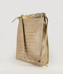 Gwyneth bag in beige, size L, with croco effect embossed. The front plate is made from cow horn. The Handbag comes with an adjustable shoulder strap. It's made from Italian calf leather. Elegant and contemporary blend.